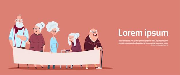 Groupe de personnes âgées tenant une bannière vide avec espace de copie grand-père et grand-mère modernes cadrage en pied Vecteur Premium