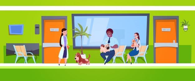 Groupe de personnes avec des chiens assis dans la salle d'attente de la clinique vétérinaire concept de médecine vétérinaire Vecteur Premium