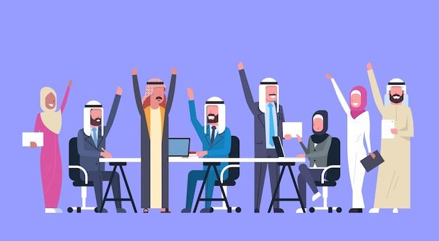 Groupe de personnes gaies de gens d'affaires arabes heureux la main levée mains ouvrières musulmanes succès d'équipe Vecteur Premium