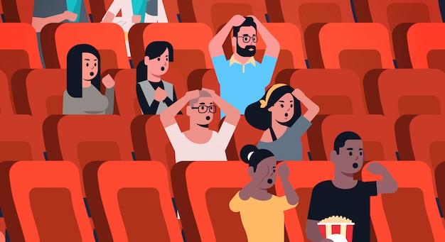 Groupe De Personnes Regardant Un Film D'horreur Et Hurlant Assis Au Cinéma Avec Du Pop-corn Et Du Cola Mix Race Hommes Femmes à La Recherche D'horreur Plat Portrait Horizontal Vecteur Premium