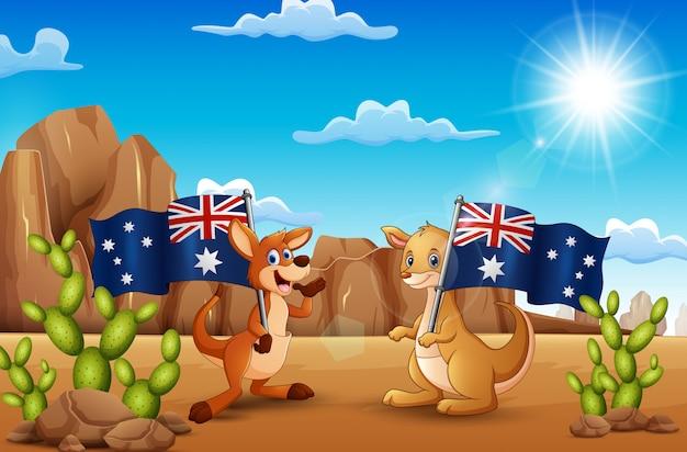 Happy australia day avec des kangourous tenant un drapeau dans le désert Vecteur Premium