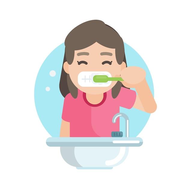 Heureuse jolie fille se brosser les dents dans la salle de bain Vecteur Premium