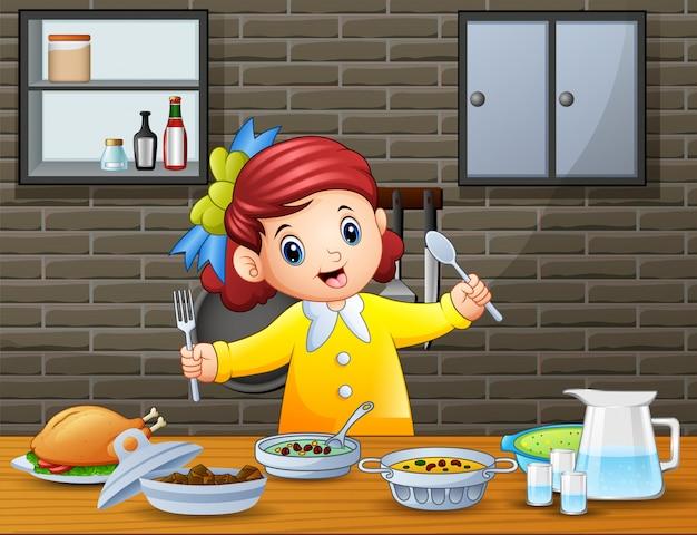 Heureuse petite fille tenant une cuillère et une fourchette à manger à la table Vecteur Premium
