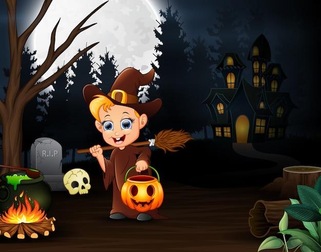 Heureuse petite sorcière tenant un panier de citrouilles dans la nuit Vecteur Premium