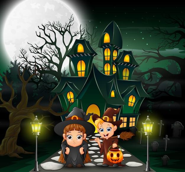 Heureux couple sorcière devant la maison hantée Vecteur Premium