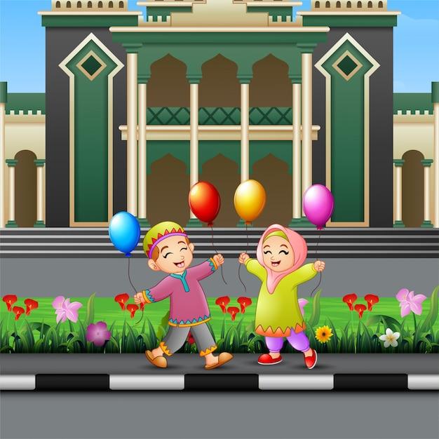 Heureux dessin animé d'enfants musulmans jouant devant une mosquée Vecteur Premium
