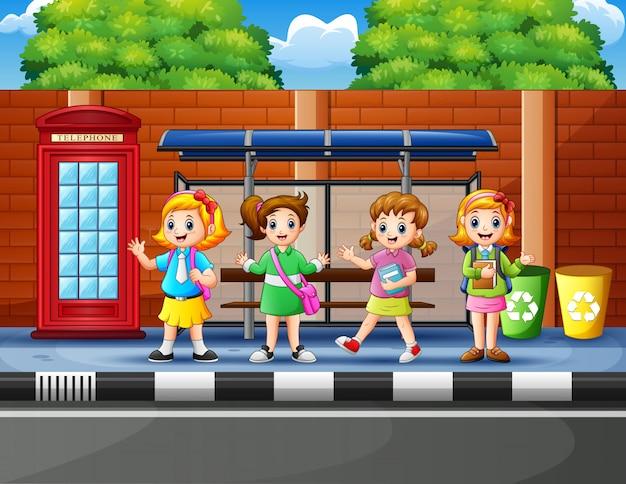 Heureux écoliers à l'arrêt de bus Vecteur Premium