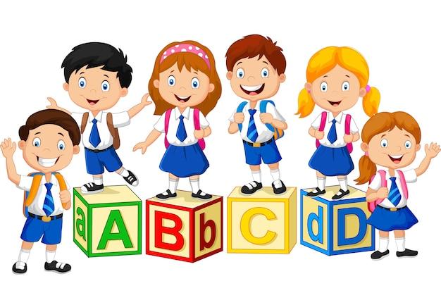 Heureux écoliers avec des blocs de l'alphabet Vecteur Premium