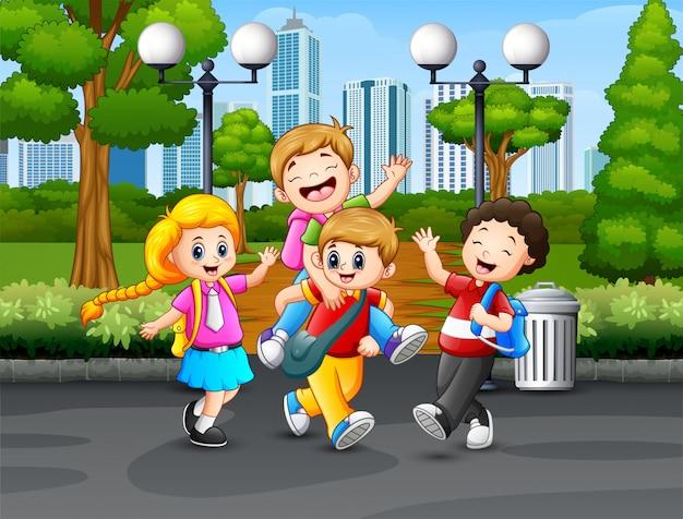 Heureux écoliers jouant dans le parc Vecteur Premium