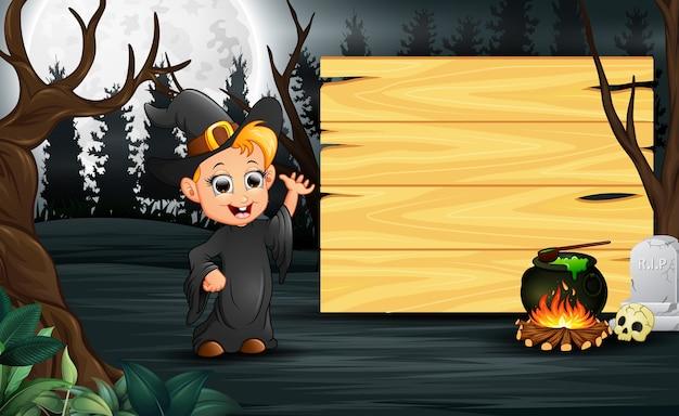 Heureux enfant portant le costume de sorcière se tenir à côté de la planche de bois Vecteur Premium