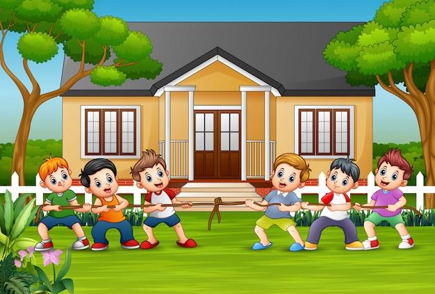 Heureux enfants jouant à la corde devant une maison Vecteur Premium