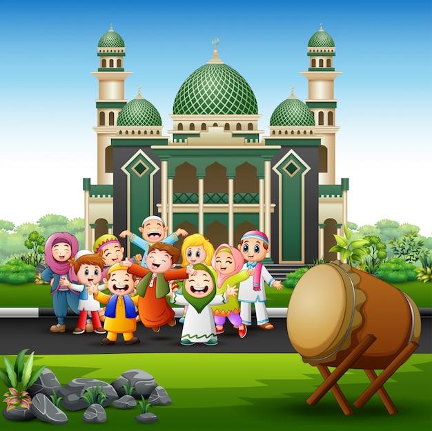 Heureux enfants musulmans cartoon devant une mosquée Vecteur Premium