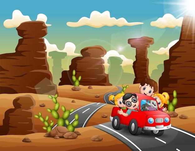Heureux enfants voyageant en voiture rouge à travers le désert Vecteur Premium
