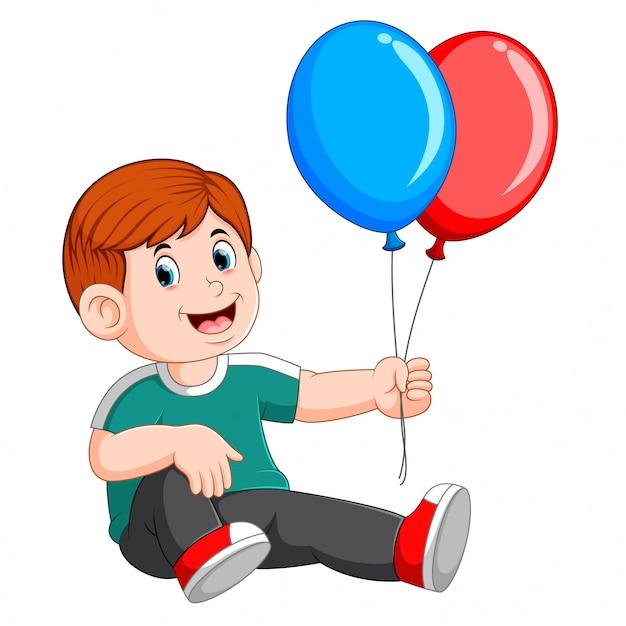 Heureux un garçon assis et portant deux ballons Vecteur Premium