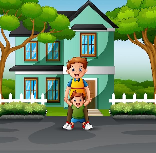 Heureux père et fils devant la maison Vecteur Premium