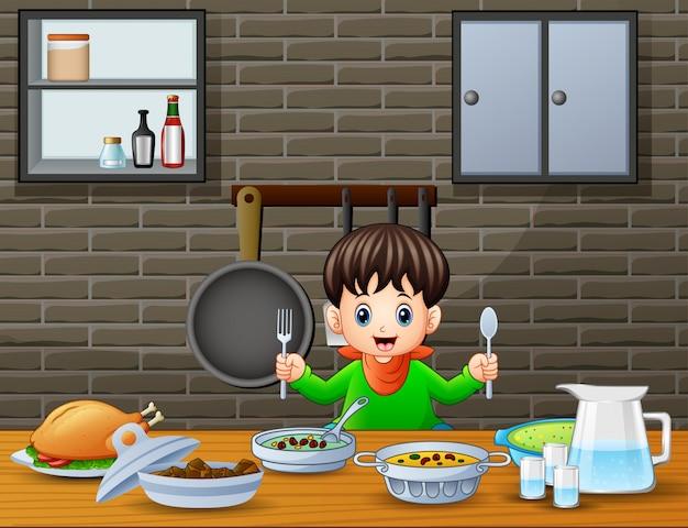 Heureux petit garçon tenant une cuillère et une fourchette à manger à la table Vecteur Premium