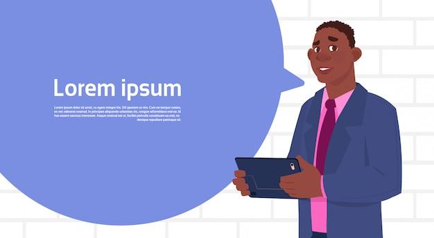 Homme d'affaires africain-américain tenant une tablette parlent une bulle de grand chat avec un espace de copie de texte Vecteur Premium