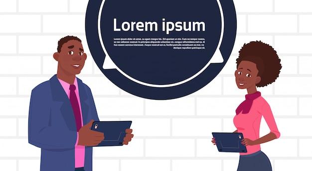 Homme d'affaires américain et femme tenant une tablette parlent une grande bulle de dialogue avec un espace de copie de texte Vecteur Premium