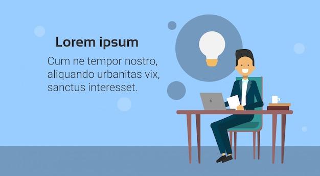Homme d'affaires assis au bureau travaillant sur un ordinateur portable à une nouvelle idée de démarrage avec bulle de lumière Vecteur Premium
