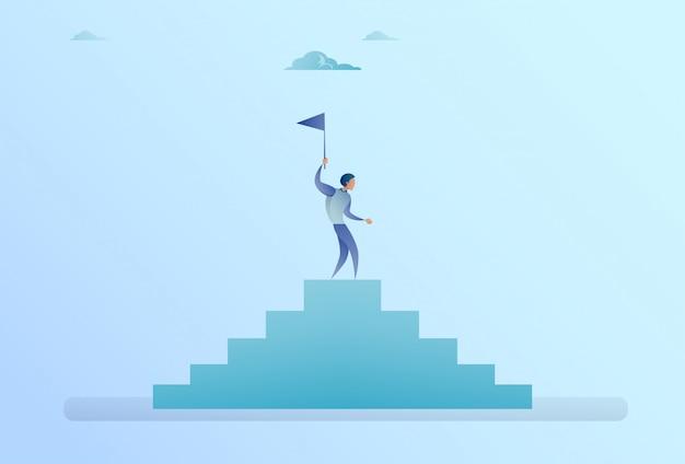 Homme d'affaires dans le haut des escaliers, tenant le concept de réussite du drapeau Vecteur Premium