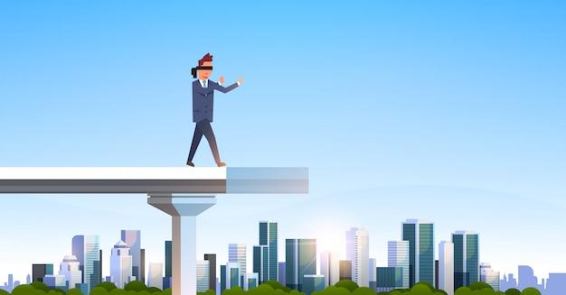 Homme d'affaires marchant les yeux bandés sur le pont cassé Vecteur Premium