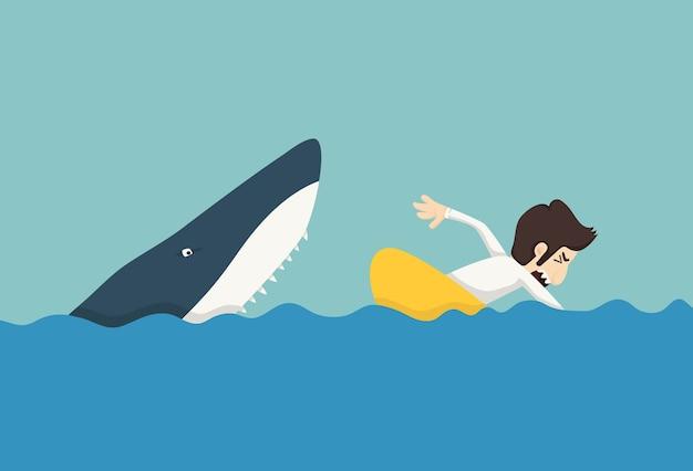Homme d'affaires nageant pour échapper aux requins Vecteur Premium