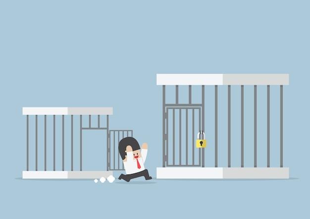 Homme D'affaires Sortant De La Petite Cage à La Plus Grande Cage Vecteur Premium