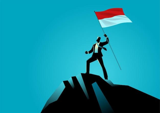 Homme D & # 39; Affaires Tenant Le Drapeau De L & # 39; Indonésie Au Sommet De La Montagne Vecteur Premium