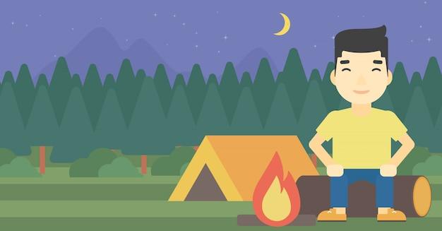 Homme assis sur un journal dans le camping. Vecteur Premium