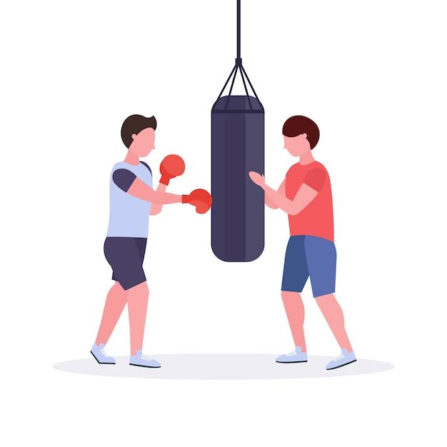 Homme Boxeur Avec Entraîneur Personnel Frappant Un Sac De Boxe En Gants De Boxe Rouges Formation De Combattant Guy Entraînement D'entraînement Club De Vie Sain Concept Fond Blanc Vecteur Premium