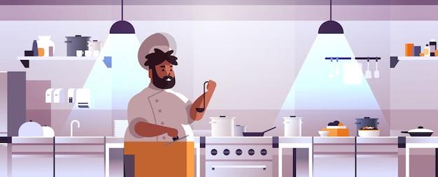 Homme Chef Cuisinier Professionnel Cuisiner Préparer Et Déguster Des Plats Homme Afro-américain En Uniforme Près Du Poêle Cuisson Concept Alimentaire Restaurant Moderne Cuisine Intérieur Plat Portrait Horizontal Vecteur Premium