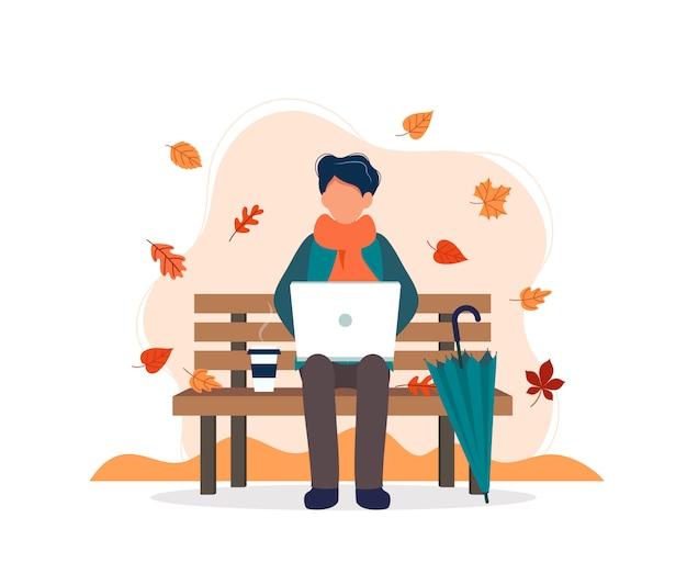 Homme avec ordinateur portable assis sur un banc en automne. Vecteur Premium