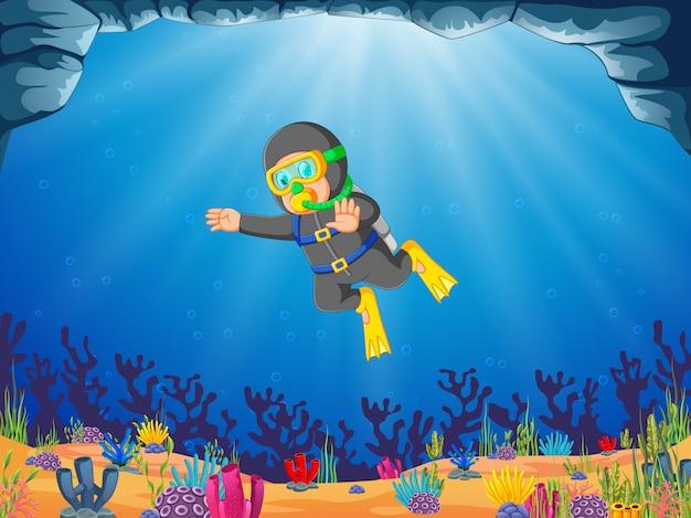 Un homme plonge sous le fond bleu de l'océan en utilisant le tube à oxygène Vecteur Premium