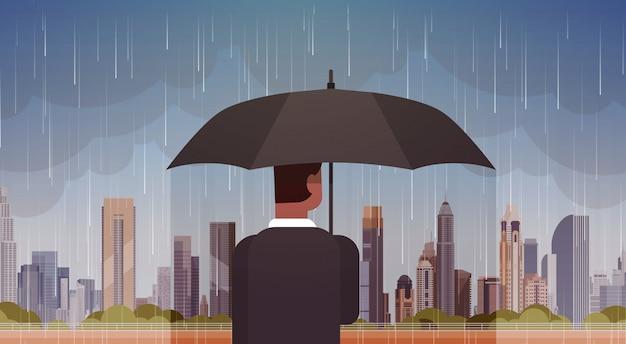 Homme tenant un parapluie regard à la tempête en ville énorme pluie fond ouragan tornade en ville concept de catastrophe naturelle Vecteur Premium