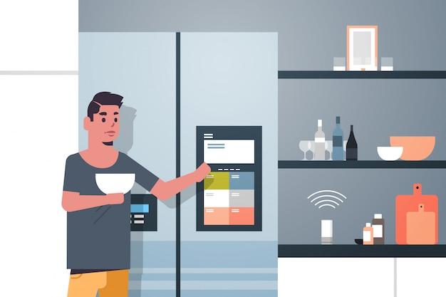 Homme Touchant L'écran Du Réfrigérateur Avec Haut-parleur Intelligent Vecteur Premium