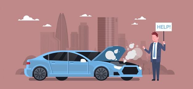 Homme avec voiture cassée tenant aide signe sur la route au-dessus de silhouette city Vecteur Premium