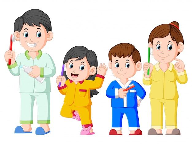 Il famille heureuse pose avec la brosse à dents Vecteur Premium