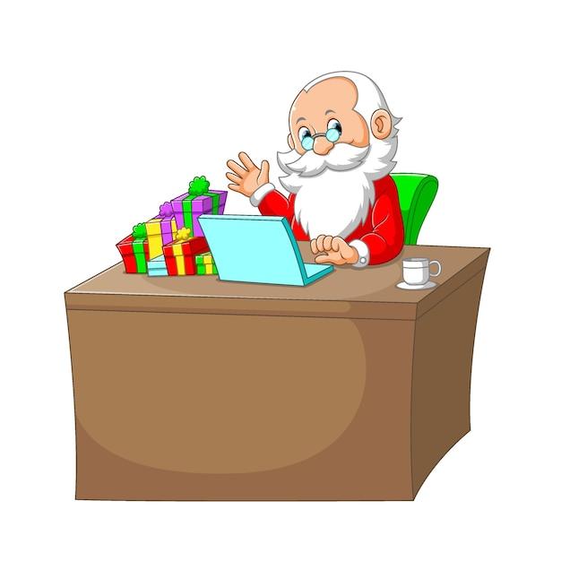 L'illustration De La Clause Du Père Noël Assis Dans Son Bureau Avec L'ordinateur Portable Et Le Cadeau Dans Son Bureau Vecteur Premium