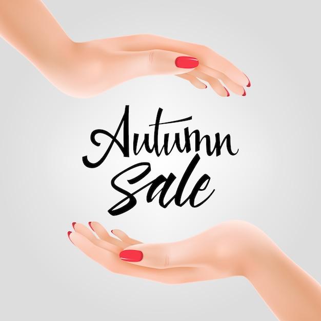 Inscription de vente d'automne entre deux mains Vecteur gratuit