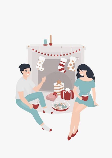Jeune couple assis au coin du feu et boit du cacao entouré de cadeaux de noël Vecteur Premium