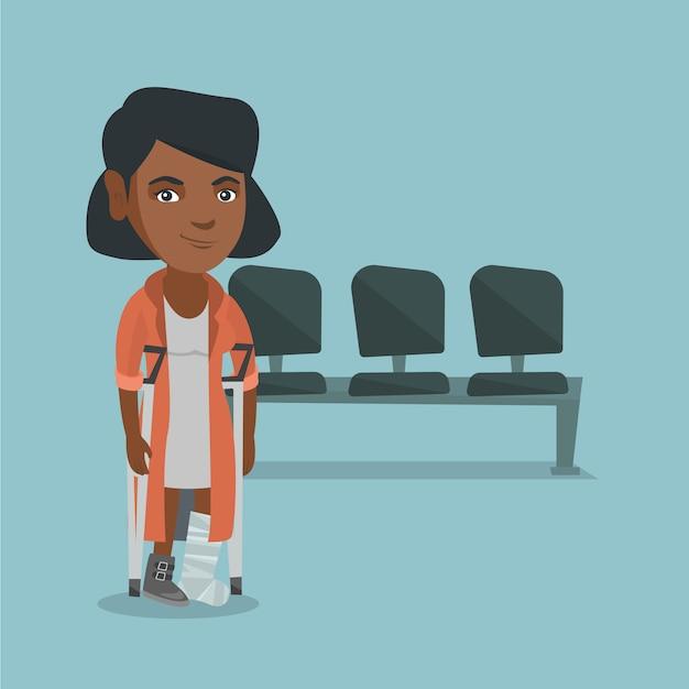 Jeune femme africaine avec une jambe cassée et des béquilles. Vecteur Premium