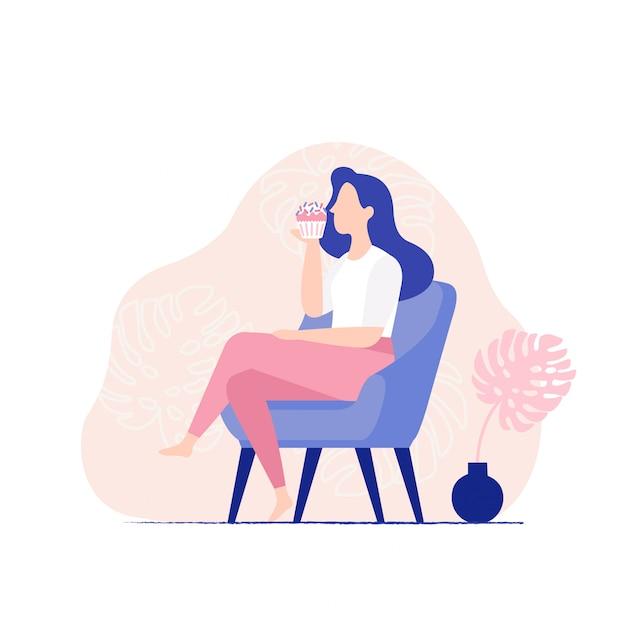 Jeune femme assise sur une chaise et mange un cupcake sucré. femme, manger, muffin, vue côté Vecteur Premium