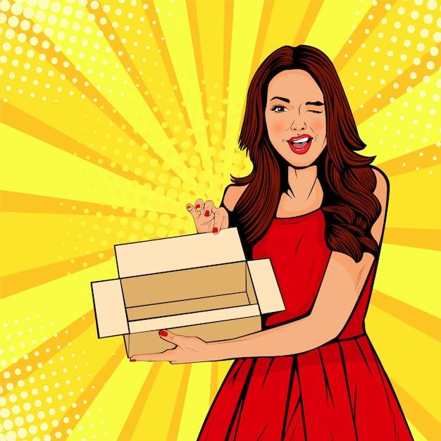 Jeune femme surprise de pop art tenant une boîte vide Vecteur Premium