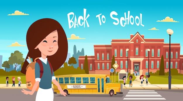 Jeune fille rentrant à l'école sur un groupe d'élèves à pied d'un bus jaune Vecteur Premium