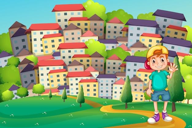 Un jeune garçon debout au sommet d'une colline à travers le village Vecteur gratuit