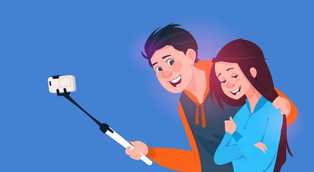 Jeune garçon et fille parlant selfie photo sur un téléphone intelligent avec un bâton Vecteur Premium