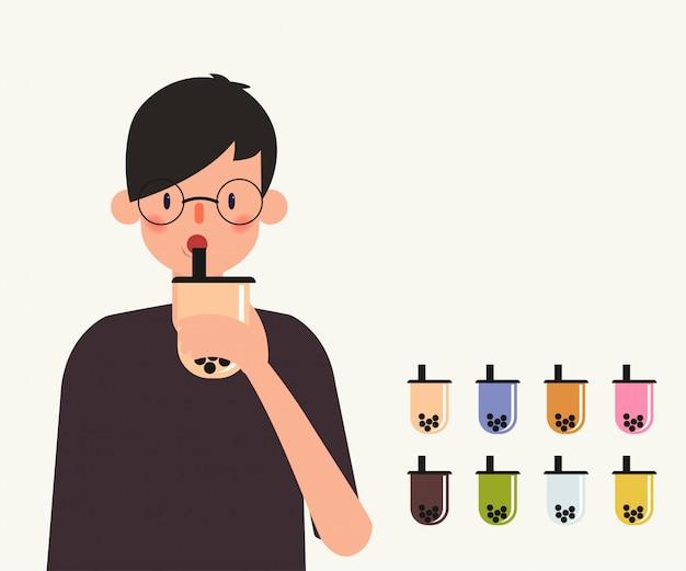 Jeune homme boire du thé au lait à bulles. Vecteur Premium