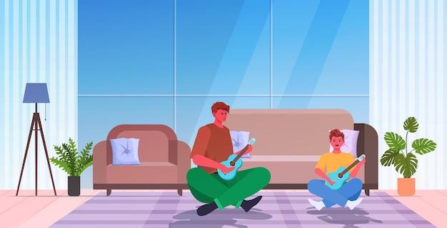 Jeune Père Enseignant Petit Fils à Jouer De La Guitare Concept De Paternité Parentale Papa Passer Du Temps Avec Son Enfant Salon Intérieur Pleine Longueur Horizontale Vecteur Premium