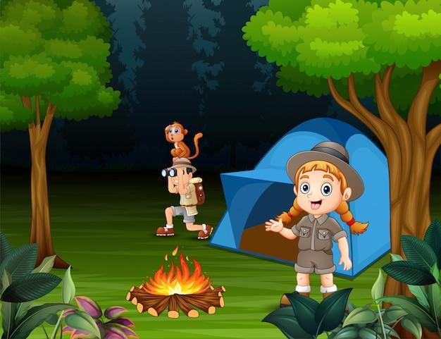 Joyeux enfants campant dans une forêt Vecteur Premium