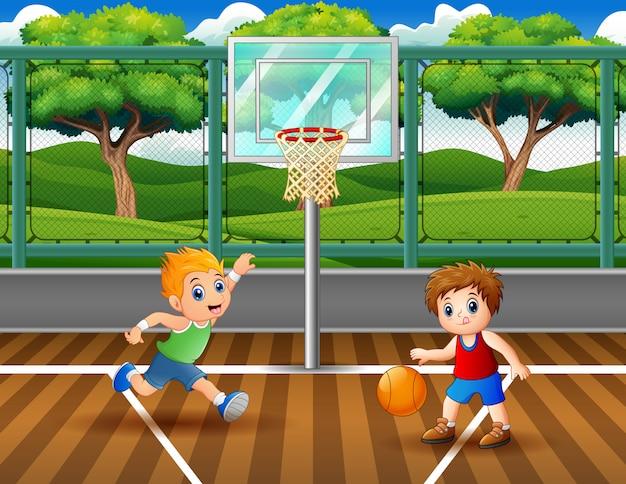 Joyeux garçons jouant au basketball sur le court Vecteur Premium